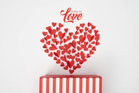 """Photo for Top view of heart shaped arrangement of small red paper cut hearts and striped gift box on white background with """"sending you love"""" lettering - Royalty Free Image"""