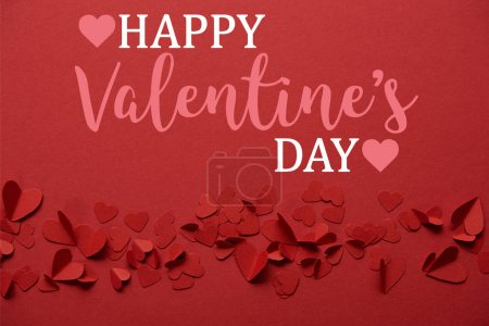 "pile of decorative paper cut hearts on red background with ""Happy valentines day"" lettering"