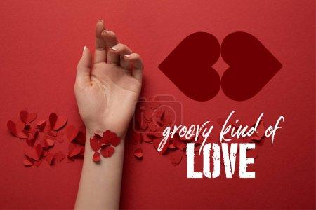 """Photo pour Vue recadrée de la main féminine avec des coeurs décoratifs coupés en papier sur fond rouge avec lettrage """"groovy kind of love"""" - image libre de droit"""