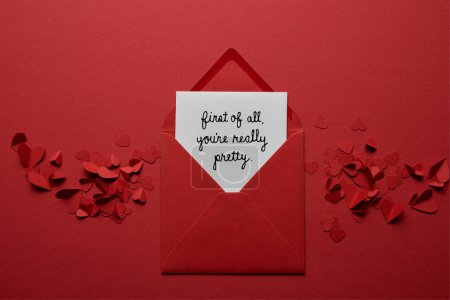 """Photo for Top view of envelope with """"first of all, you are really pretty"""" lettering, with paper cut hearts on red background - Royalty Free Image"""