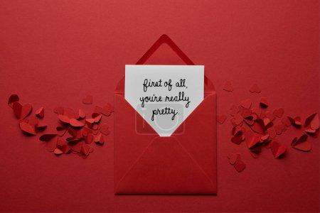 Photo pour Vue de dessus d'enveloppe avec «tout d'abord, tu es vraiment jolie» lettrage, avec papier coupe des coeurs sur fond rouge - image libre de droit
