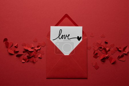 "Photo for Top view of envelope with ""love"" lettering, with paper cut hearts on red background - Royalty Free Image"