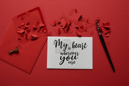 "Photo for Top view of envelope with ""my heart is wherever you are"" lettering , paper cut hearts and pen on red background - Royalty Free Image"