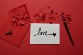 """Постер, картина, фотообои """"вид сверху конверт с буквами «любовь», бумаги вырезать сердца и пера на красном фоне"""""""