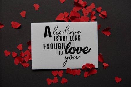 Photo pour Vue de dessus de la carte de voeux avec l'inscription «sa vie n'est pas assez long pour vous aimer» et papier rouge coupe des coeurs sur fond noir - image libre de droit