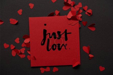 """Foto de Vista superior de la tarjeta de felicitación roja con letras de """"simplemente amor"""" y el papel corta corazones sobre fondo negro - Imagen libre de derechos"""