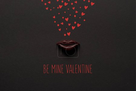 """Photo for Top view of tasty chocolate lips on black background with """"be mine valentine"""" lettering - Royalty Free Image"""