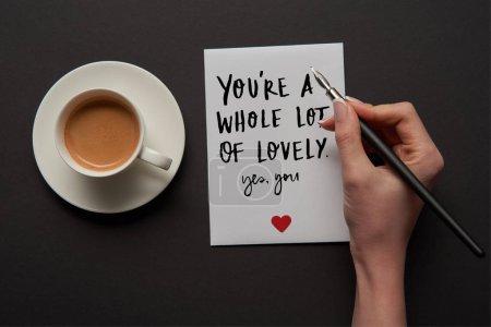 """Photo pour Vue recadrée de femme écrivant sur la carte de vœux """"vous êtes beaucoup de belle, oui vous"""" lettrage avec signe de coeur rouge près de tasse de café - image libre de droit"""