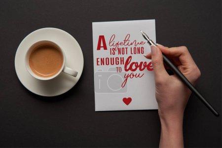 """Photo pour Vue recadrée de femme écrivant sur la carte de vœux """"une vie n'est pas assez longue pour vous aimer"""" lettrage avec signe de coeur rouge près de tasse de café - image libre de droit"""