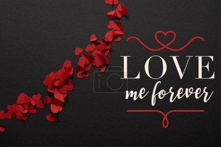 """Photo for Top view of red small paper cut hearts on black background with """"love me forever"""" lettering - Royalty Free Image"""
