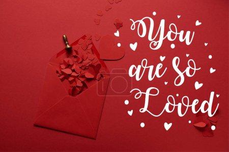 Photo pour Vue de dessus du papier coupe des coeurs et ouvert l'enveloppe sur fond rouge avec «tu es tellement aimé» lettrage - image libre de droit