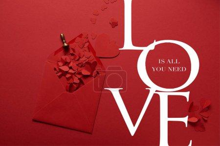 """Photo pour Vue du haut des coeurs coupés en papier et enveloppe ouverte sur fond rouge avec lettrage """"L'amour est tout ce dont vous avez besoin"""" - image libre de droit"""