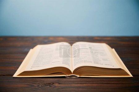 Photo pour Focus sélectif du livre sur table en bois avec espace de copie isolé sur bleu - image libre de droit