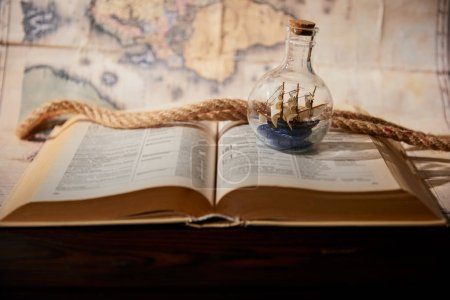 Photo for Selective focus of toy ship in glass bottle, book, map and rope on table - Royalty Free Image
