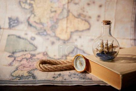 Photo pour Concentration sélective du navire jouet en bouteille, livre, carte, boussole et corde en verre - image libre de droit