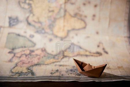 Photo pour Mise au point sélective de carte et papier bateau sur table en bois - image libre de droit