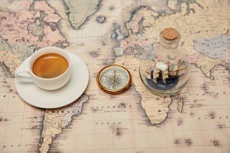 Photo pour Mise au point sélective du café tasse et soucoupe, boussole et jouet bateau en bouteille en verre sur la carte - image libre de droit