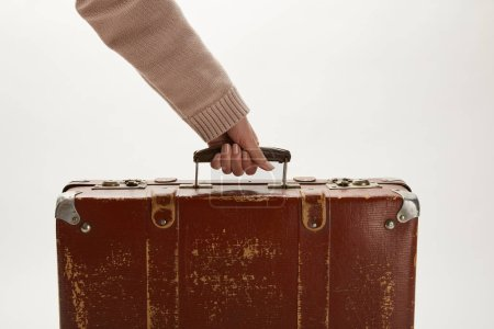 Photo for Partial view of woman holding brown suitcase isolated on grey - Royalty Free Image