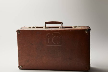 vintage leather brown suitcase on grey background