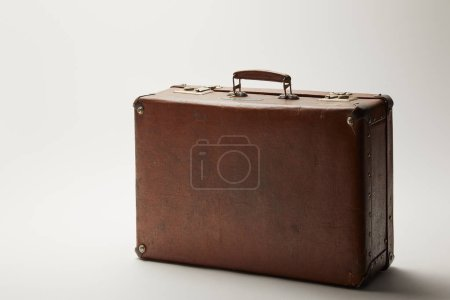 retro leather brown suitcase on grey background