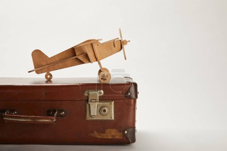 toy plane and leather suitcase on grey background with copy space