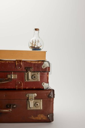 Photo for Toy ship in glass bottle and book on brown suitcases with copy space - Royalty Free Image