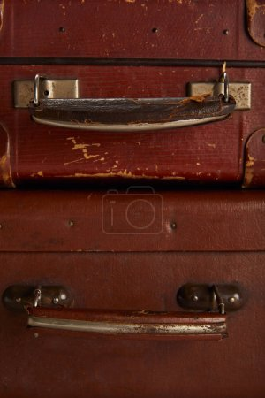 close up of handles of brown leather suitcases