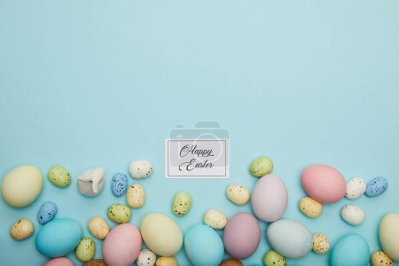 Photo for Top view of toy bunny, painted easter and quail eggs and card with happy easter lettering - Royalty Free Image