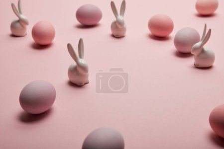 Photo for Toy bunnies and painted easter eggs on pink background - Royalty Free Image