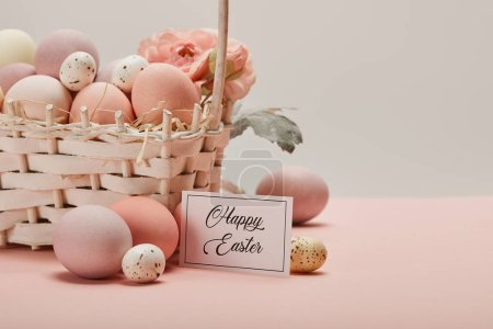 Photo for Easter chicken and quail eggs in straw basket with flower and card with happy easter lettering - Royalty Free Image