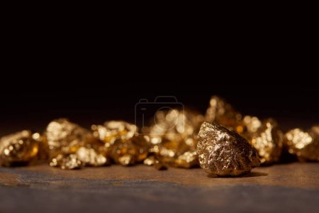 Photo for Selective focus of golden stones on dark marble isolated on black - Royalty Free Image
