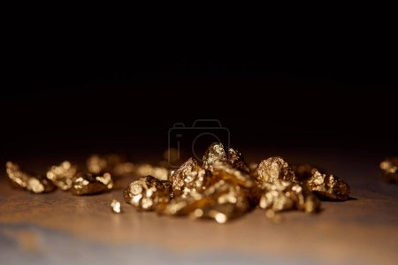 Photo for Selective focus of golden stones on grey and brown marble surface with blurred black background - Royalty Free Image