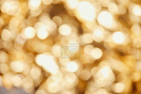 Photo pour Bright blurred twinkles and sparkles on golden background - image libre de droit