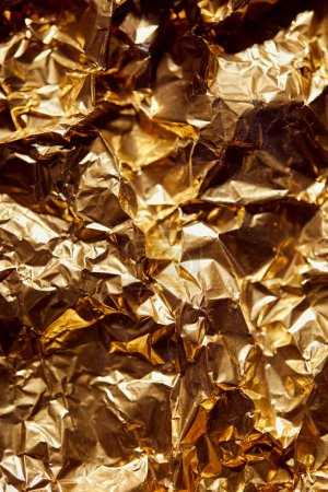 crumpled golden foil sheet with bright twinkles and shadows