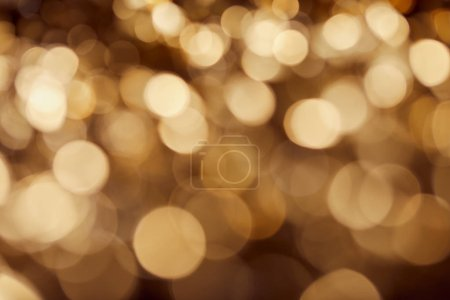 Photo for Dark background with bright blurred golden twinkles and sparkles - Royalty Free Image