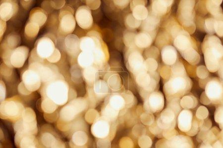 Photo pour Blurred golden twinkles and sparkles on dark background - image libre de droit