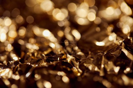 Photo for Selrctive focus of foil with golden sparkling lights in shadows - Royalty Free Image