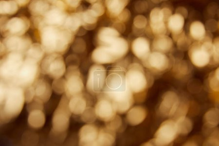 Photo for Blurred bright twinkles and sparkles on golden background - Royalty Free Image