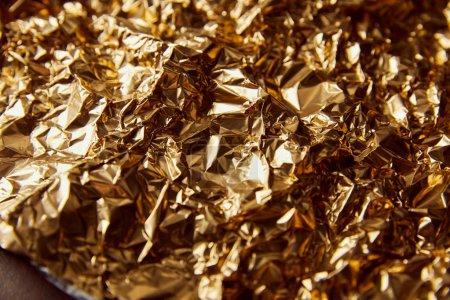 Photo pour Feuille d'or plissée avec des scintillements sur la surface brune - image libre de droit