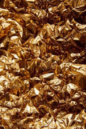 Photo pour Feuille d'or froissée avec des reflets et des étincelles - image libre de droit