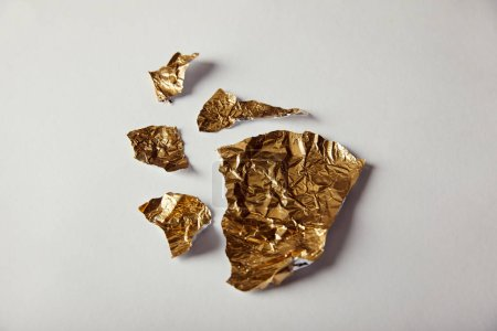 top view of pieces golden foil on white background