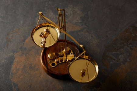 Photo for Golden stones on scales on grey and brown marble table - Royalty Free Image