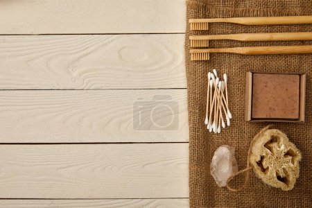 Photo for Flat lay of various hygiene and care items arranged on sackcloth on white wooden surface, zero waste concept - Royalty Free Image