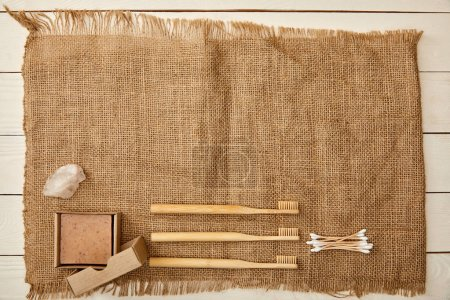 Photo for Top view of different hygiene and care items arranged on sackcloth on white wooden surface, zero waste concept - Royalty Free Image