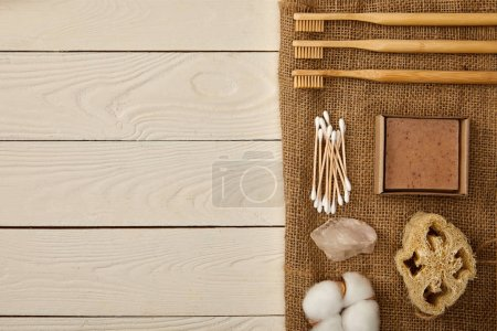 Photo pour Flat lay of different hygiene and care items arranged on sackcloth on white wooden surface, zero waste concept - image libre de droit