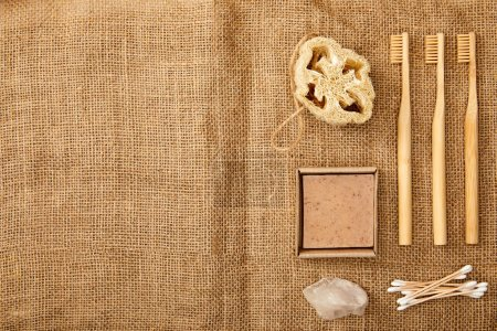 Photo for Top view of different hygiene and care items on brown sackcloth surface, zero waste concept - Royalty Free Image