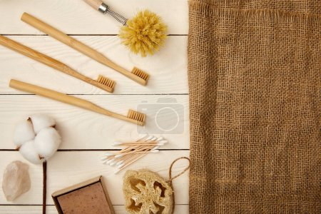 Photo for Flat lay of different hygiene and care items, and piece of sackcloth on white wooden surface, zero waste concept - Royalty Free Image
