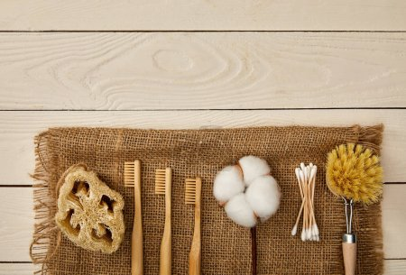 Photo for Flat lay of  hygiene and care items arranged on sackcloth on white wooden surface, zero waste concept - Royalty Free Image
