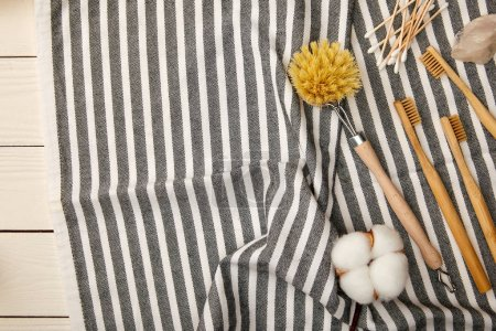 Photo pour Top view of hygiene and care items on striped towel on white wooden surface, zero waste concept - image libre de droit