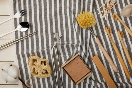 Photo pour Top view of cutlery, hygiene and care items on striped towel on white wooden surface, zero waste concept - image libre de droit